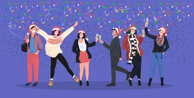 Businesspeople in santa chapeaux ayant des confettis fête d'entreprise gens d'affaires célébrant joyeux noël bonne année concept de vacances d'hiver