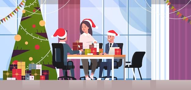 Businesswoman féliciter ses collègues masculins avec joyeux noël bonne année vacances les gens d'affaires au lieu de travail tenant des coffrets cadeaux intérieurs de bureau moderne