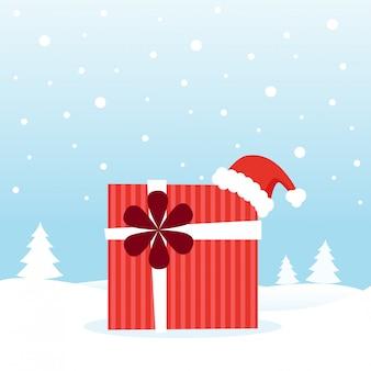 Cadeau avec bonnet de noel sur la neige