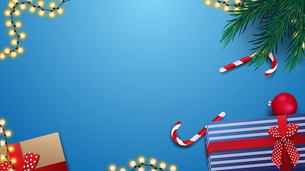 Cadeaux, canne en bonbon, branche de noël et guirlande sur fond de table bleu