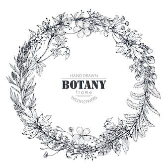 Cadre avec des éléments d & # 39; herbes et de fleurs sauvages disposés sur une forme de couronne
