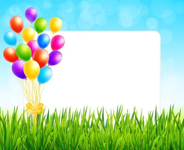 Cadre avec feuille de papier et ballons colorés sur l'herbe verte