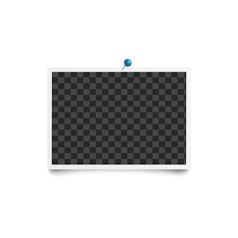 Cadre horizontal de photo vierge de l'album épinglé au mur blanc avec broche bleue