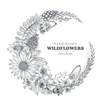 Cadre vectoriel avec des éléments d'herbes et de fleurs sauvages disposés sur une forme de couronne pour les invitations de mariage et les cartes d'anniversaire.