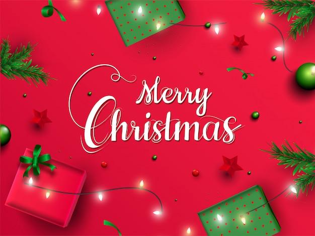 Calligraphie de joyeux noël avec vue de dessus de boîtes-cadeaux, étoiles, feuilles de pin et guirlande d'éclairage décorées sur le rouge.