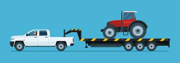 Une camionnette tracte un tracteur sur une remorque isolée