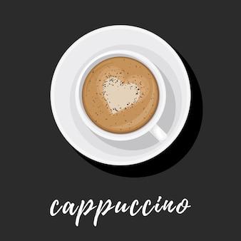Cappuccino en tasse blanche sur soucoupe avec motif coeur sur la mousse et saupoudré de chocolat.