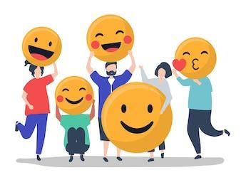 Caractères des personnes tenant une illustration d'émoticônes positives