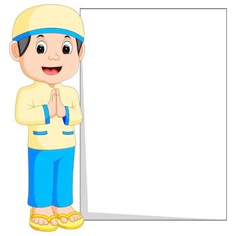Caricature de garçon musulman heureux tenant une pancarte blanche