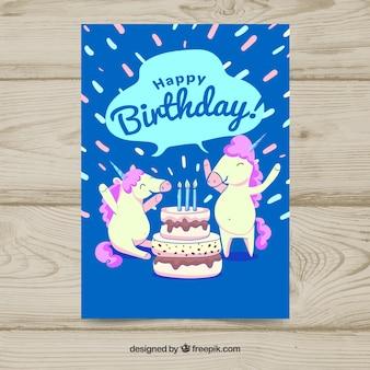 Carte d'anniversaire avec des licornes et un gâteau heureux
