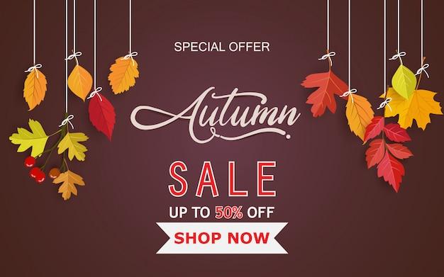 Carte brune avec des feuilles d'automne suspendue à un fil