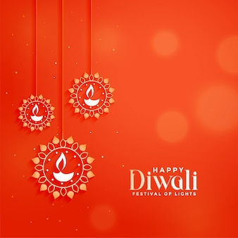 Carte de fête diwali orange avec lampes diya suspendues