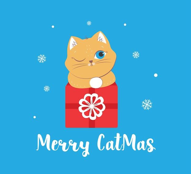La carte de joyeux noël avec tête de chat sur le présent les animaux d'hiver avec la phrase de lettrage