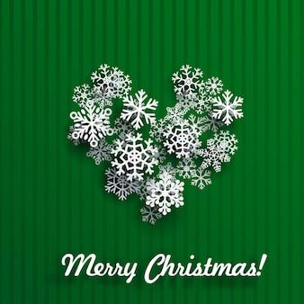 Carte de noël avec coeur fait de flocons de neige blancs sur fond rayé vert
