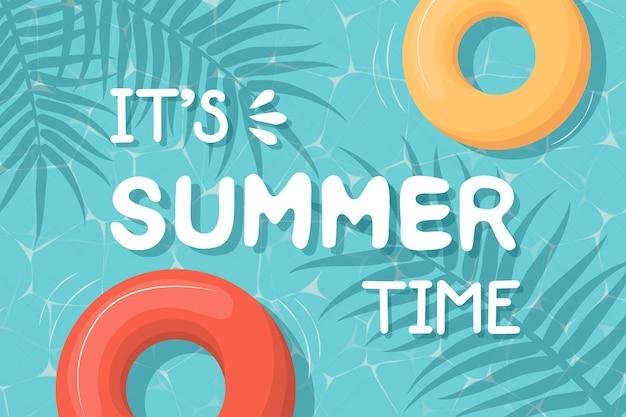 Carte postale avec lettrage c'est l'heure d'été. piscine avec anneaux et feuilles gonflables