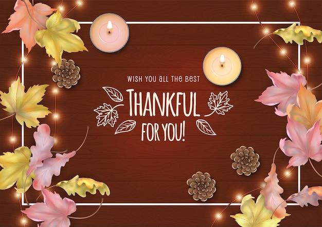 Carte de thanksgiving heureux avec des feuilles mortes, des bougies et des cônes sur un fond en bois
