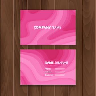 Carte de visite rose avec fond avec des formes de papier de couleur rose foncé découpées dans un style d'art abstrait en papier 3d