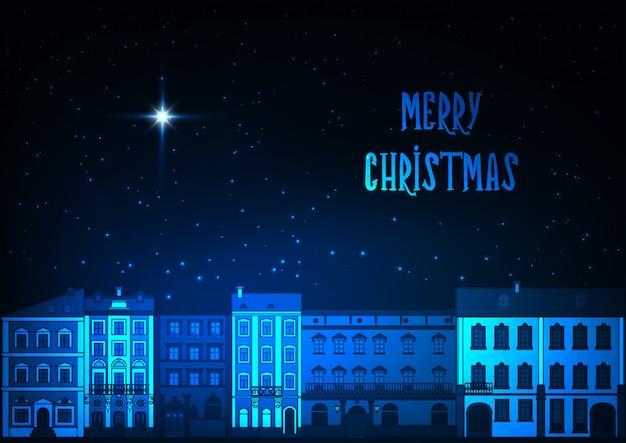 Carte de voeux joyeux noël avec les anciens bâtiments de la ville européenne, ciel étoilé sur bleu foncé.