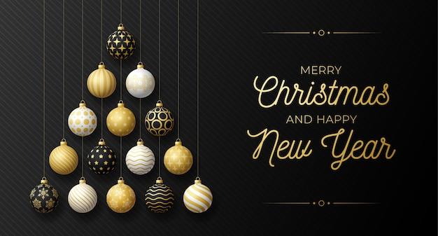 Carte de voeux de luxe de noël et du nouvel an. arbre de noël créatif fait de boules dorées, noires et blanches brillantes sur fond noir pour la célébration de noël et du nouvel an.