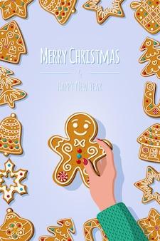Carte de voeux de noël avec main de femme tenant l'homme en pain d'épice sur fond bleu. biscuits de fête en forme de cloches et de maisons, d'étoiles et de flocons de neige, d'arbres et de coffrets cadeaux. illustration vectorielle de dessin animé