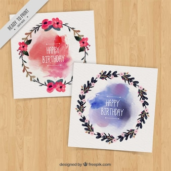 Les cartes d'anniversaire avec des couronnes de fleurs avec des taches d'aquarelle