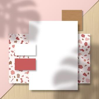 Cartes de visite et papier à en-tête sur carrelage à motif terrazzo et surface de surface avec une superposition d'ombre de feuilles de palmier monstera