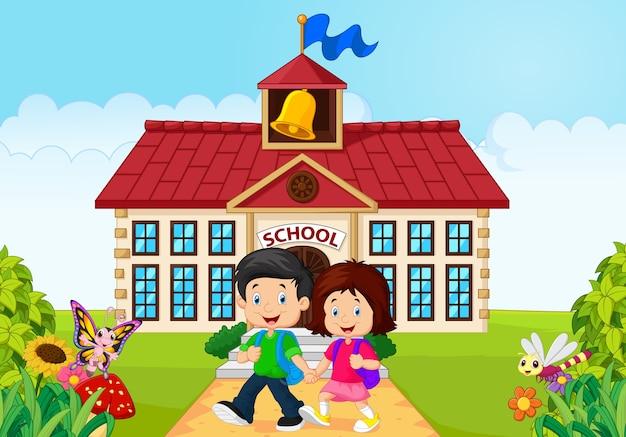 Cartoon petits enfants heureux sur fond de bâtiment scolaire