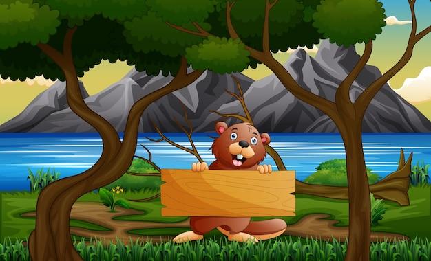 Un castor tenant une pancarte en bois sous l'arbre