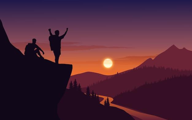 Célébration de grimpeur au sommet de la falaise au coucher du soleil