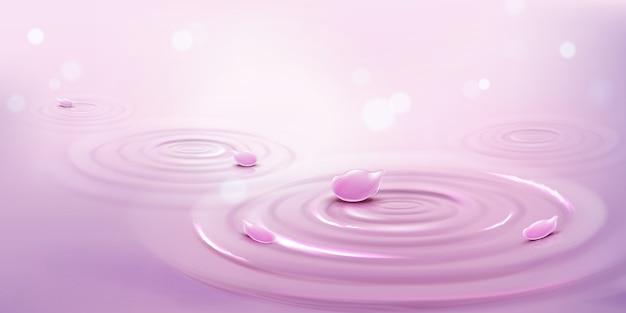Cercles sur l'eau et pétales de fleurs roses, fond de vagues