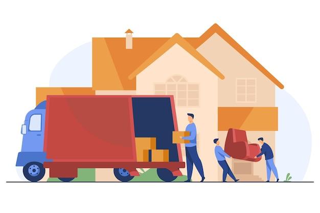 Chargeurs transportant un fauteuil et des boîtes dans une nouvelle maison