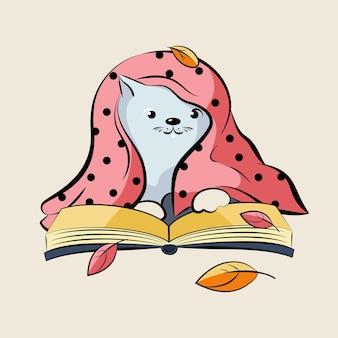 Un chaton mignon lit un livre sous un plaid.