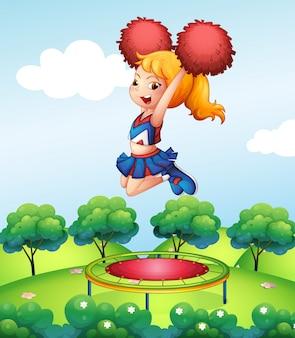 Une cheerdancer tenant ses pompons rouges au-dessus du trampoline