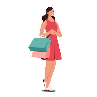Cheerful girl shopaholic avec des achats dans des sacs en papier colorés
