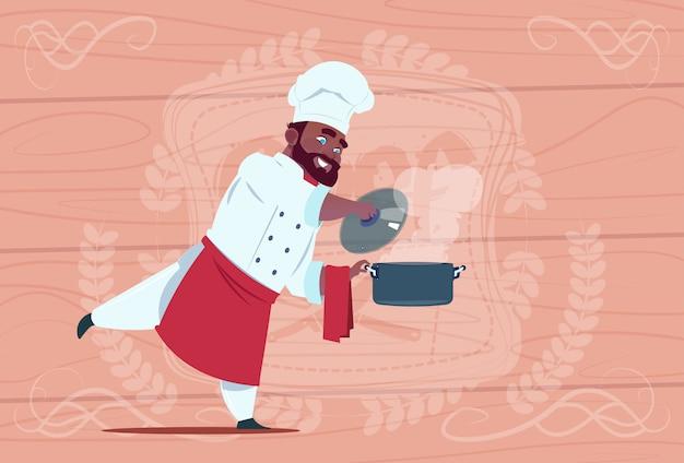 Chef afro-américain cuisinier tenant une casserole avec soupe chaude souriant chef de bande dessinée en uniforme de restaurant blanc sur fond texturé en bois
