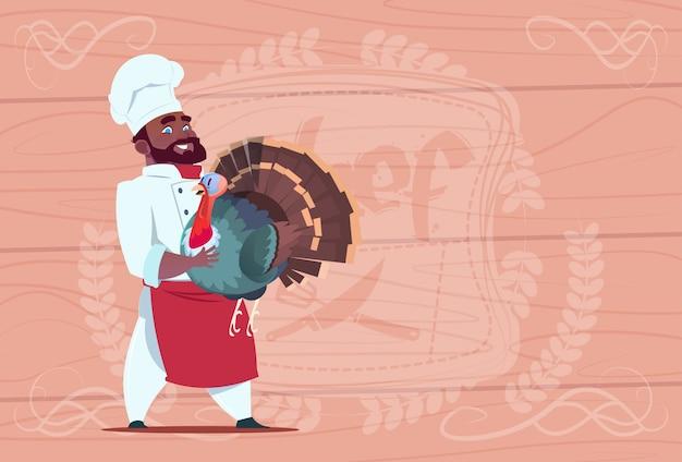 Chef américain afro-américain cuisinier cuire turquie souriant chef de restaurant de bande dessinée en uniforme blanc sur fond texturé en bois
