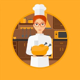 Chef cuisinier tenant le poulet rôti.