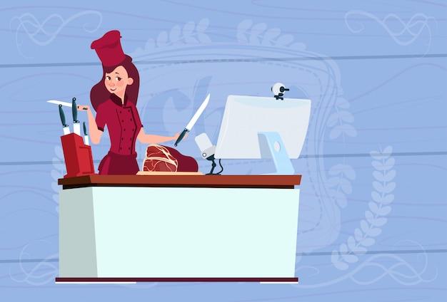 Chef féminin cuisinant devant la caméra web sur un ordinateur faisant un blog vidéo culinaire