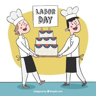 Des chefs heureux portant le gâteau de la journée du travail