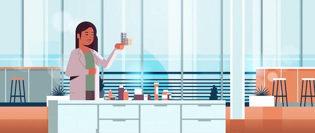 Chercheur scientifique détenant des paquets de médicaments