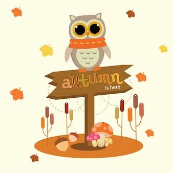 Chouette debout sur le signe de l'automne