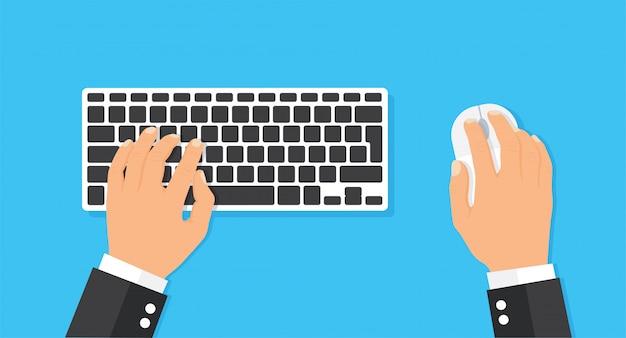 Clavier et souris d'ordinateur avec les mains de l'utilisateur