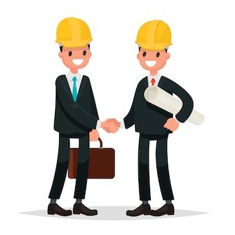 Le client et l'entrepreneur. hommes de poignée de main vêtus de costumes et de casques.
