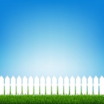 Clôture blanche avec herbe verte et ciel bleu