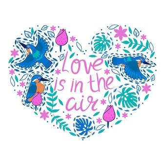 Coeur avec martins-pêcheurs et feuilles tropicales et l'inscription amour dans l'air.