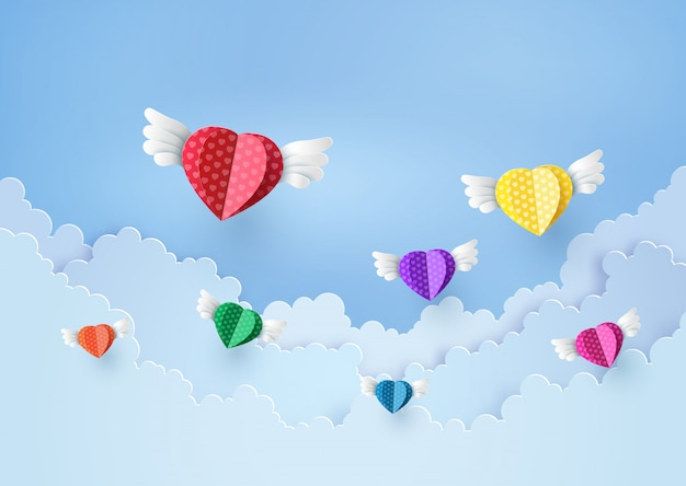 Coeur de papier coloré volant sur le ciel