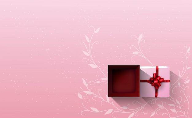 Un coffret cadeau blanc noué avec un ruban rouge ouvert sur fond rose.