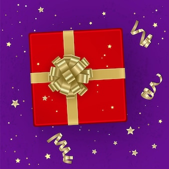Un coffret cadeau rouge réaliste orné d'un arc en or, vue de dessus.