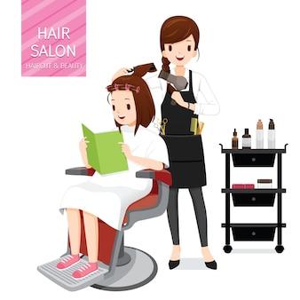 Coiffeur faisant des cheveux client féminin dans un salon de coiffure