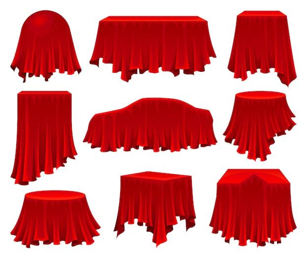 Collection d'objets cachés sous un tissu rouge.
